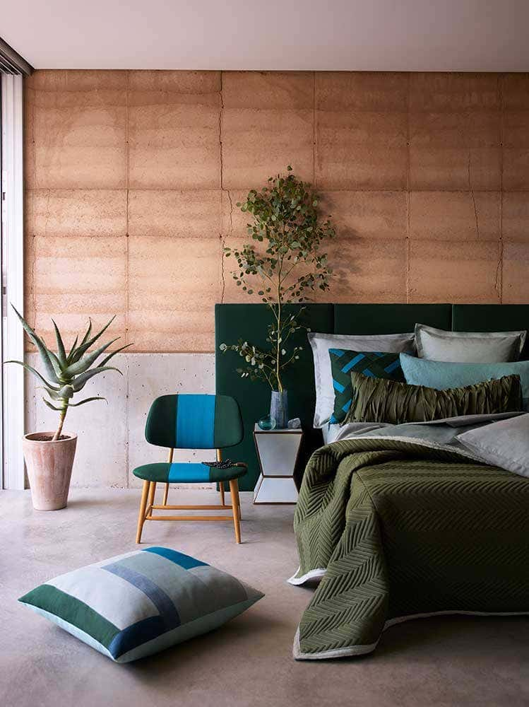 Bedroom with plant décor and green Sunbrella fabric