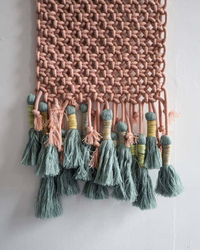 Textile wall décor with tassels made out of Sunbrella fabric