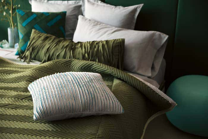 Bed with olive green comforter and green accent pillows