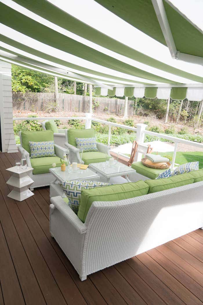 Upstairs patio with outdoor wicker furniture covered by a striped Sunbrella retractable awning