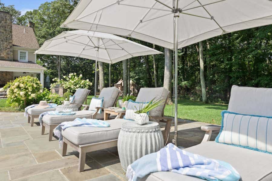 Outdoor pillows and throws make for a seamless transition from indoor to outdoor living in this poolside patio.