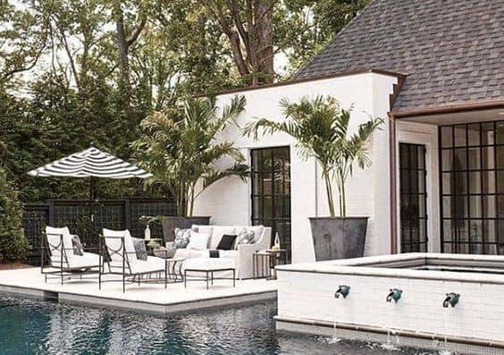 Black and white Sunbrella furnishings complete this modern poolside entertaining space.