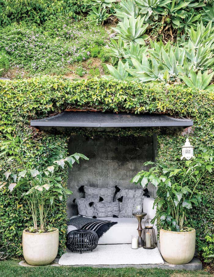 Black and white Sunbrella fabrics highlight the surrounding lush greenery in this outdoor nook.