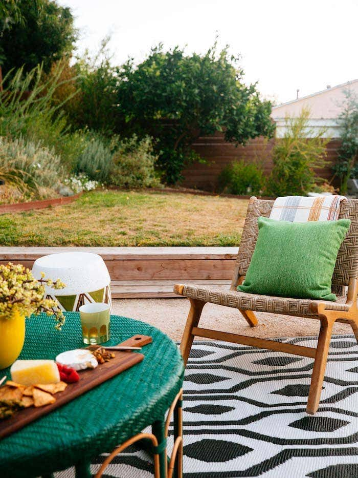 Vibrant green Sunbrella fabric accent pillows add a pop of color while a black and white patterned outdoor rug creates an eclectic outdoor design.