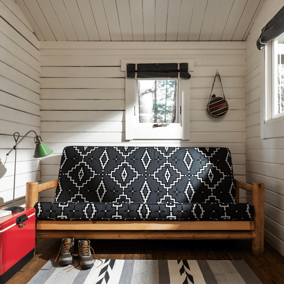 Futon upholstered with Pendleton by Sunbrella collection fabric in Kiva Steps, a black and white pattern.