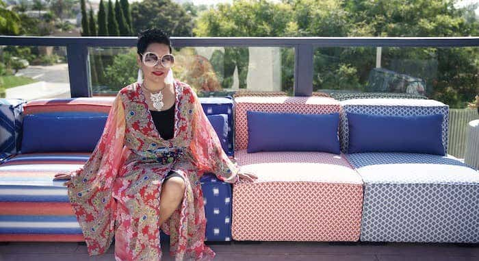 Interior designer Rachel Moriarty sits on modular style seating in rooftop space, upholstered in colorful Sunbrella textiles
