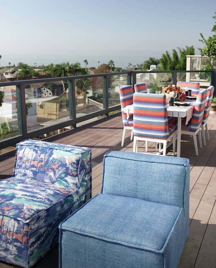 Sunbrella performance fabrics in coastal blues and oranges are featured in this California rooftop dining space