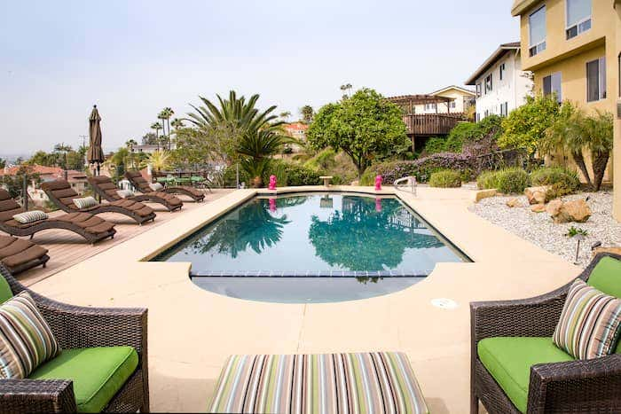 Poolside entertaining space shows bright, colorful Sunbrella stripe patterns on wicker seating and central ottoman