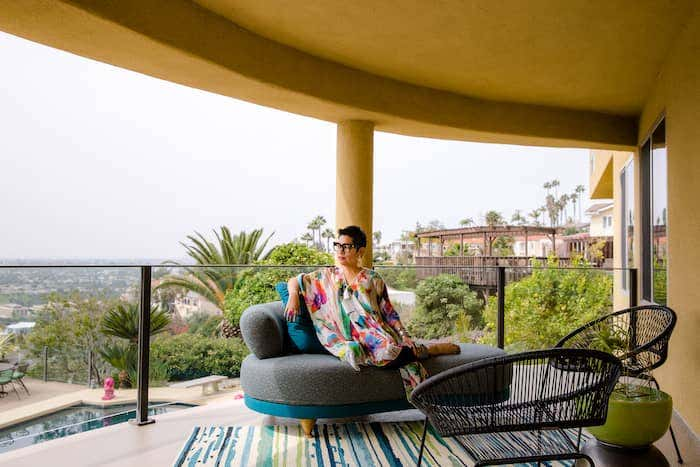 This home's covered terrace features geometric furniture, upholstered in Sunbrella fabric, and a coastal scenic view in the distance