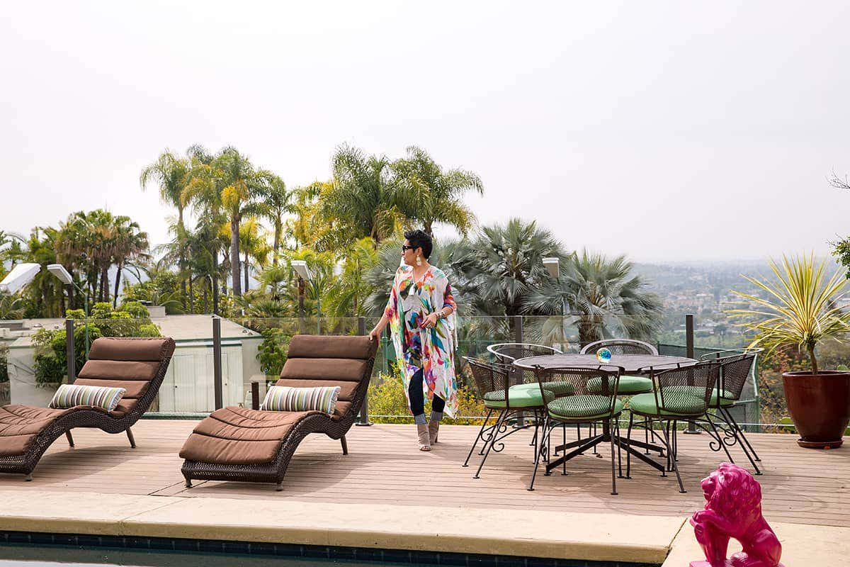 Designer Rachel Moriarty looks out onto coastline from the poolside terrace, featuring Sunbrella performance fabrics in colorful stripes
