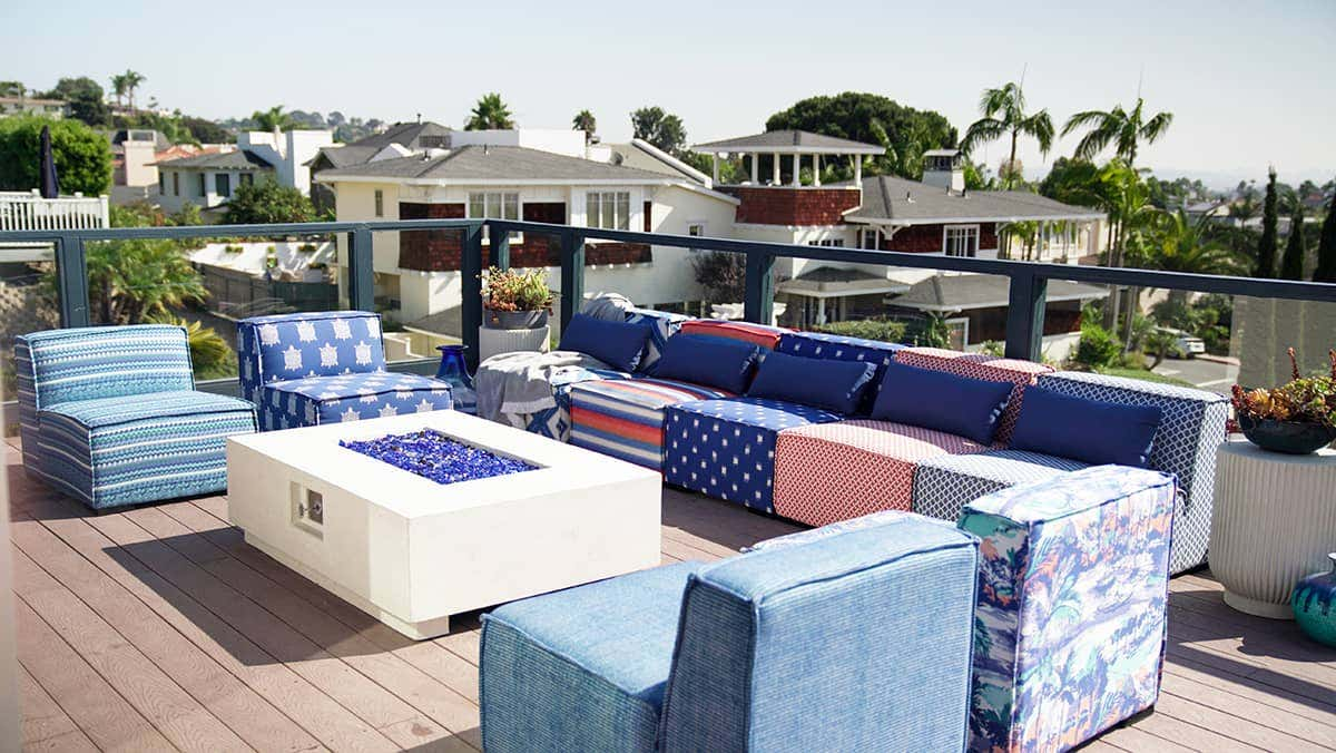 Symmetrical seating surrounds a fire pit, upholstered in Sunbrella fabrics featuring blue tones and coastal patterns