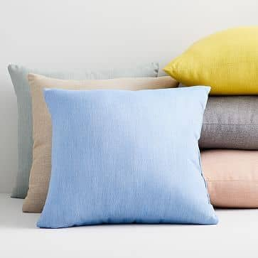 Colorful Sunbrella performance fabric pillows from West Elm are the perfect addition to a kid-friendly living room.