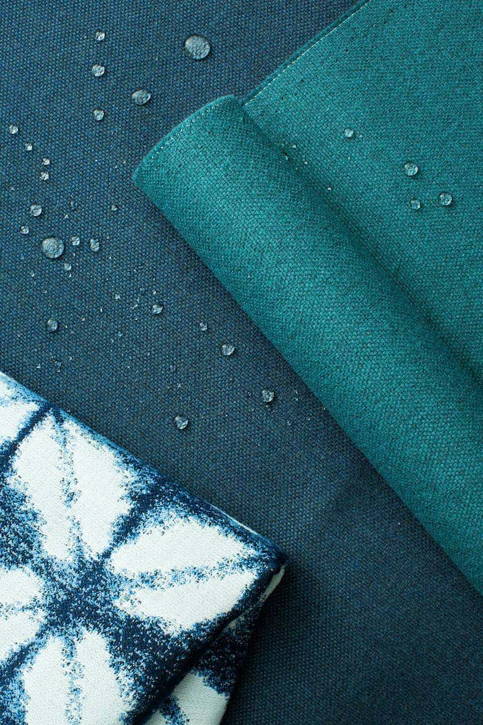 Detail shot of Sunbrella fabrics in shades of blue with water droplets to show water resistant capabilities.
