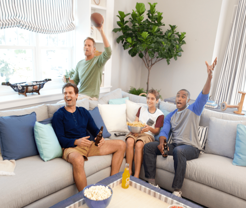 Passionate football fans cheer on their team on worry-free Sunbrella upholstered sofa while hosting a Super Bowl party