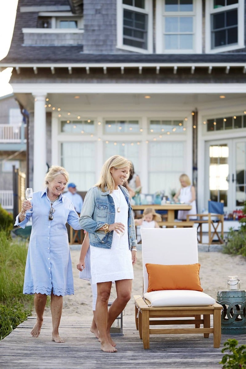Women outside drinking wine walking towards a lounge chair upholstered in white Sunbrella fabric and an orange Sunbrella fabric pillow,
