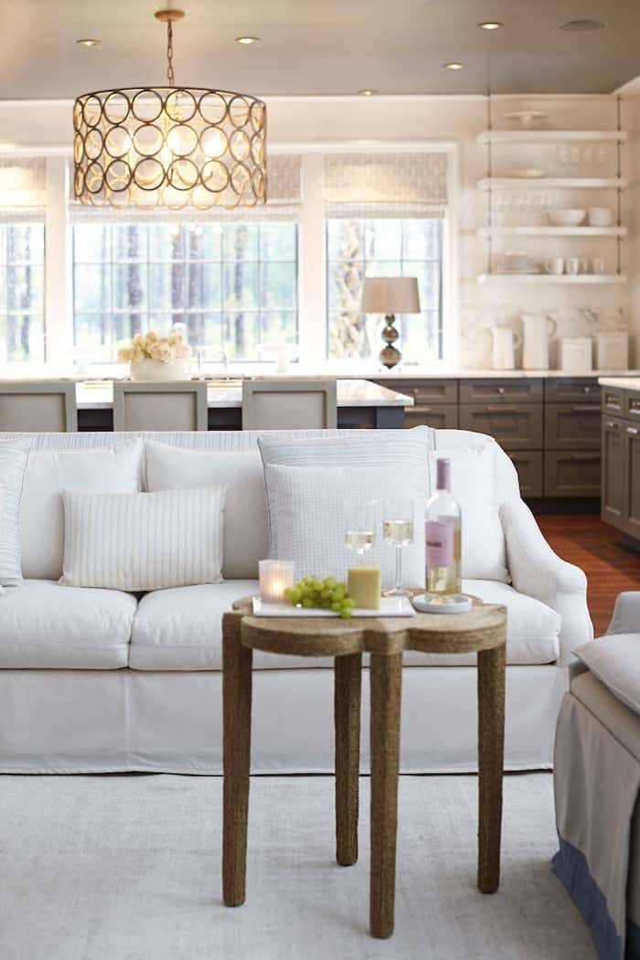 Living room with Sunbrella upholstered sofa in white and a table with a bottle of wine.