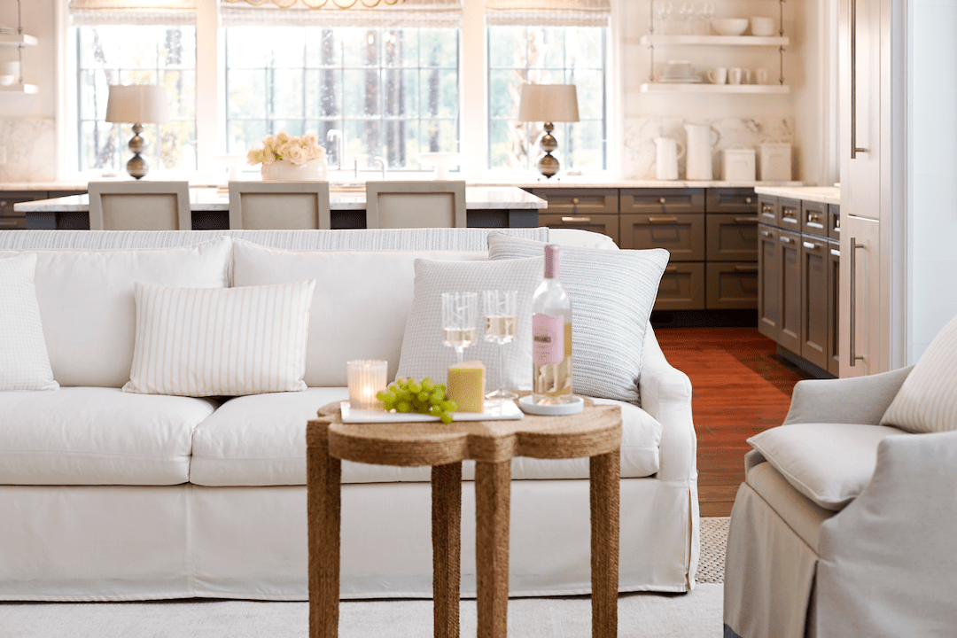 Living room sofa upholstered in white Sunbrella fabrics and a table with two glasses and a bottle of wine