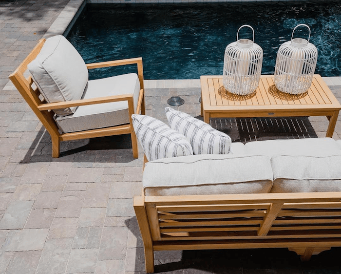 Teak wood outdoor patio furniture set by the pool with neutral Sunbrella outdoor upholstery fabric cushions and pillows
