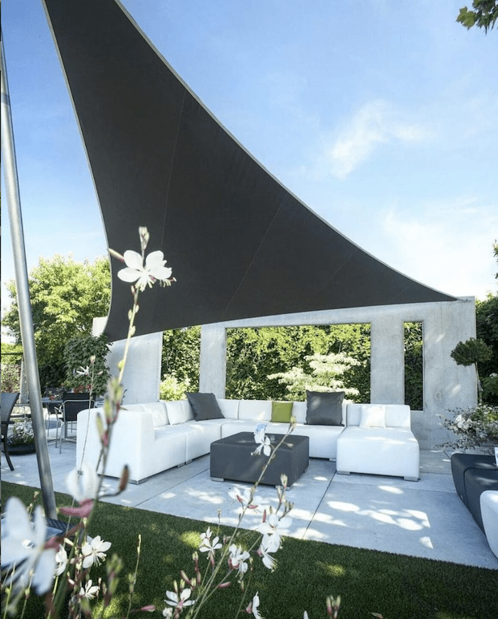 Outdoor living space with a white outdoor sofa and Sunbrella shade sail fabric
