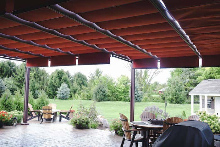 Rich red Sunbrella fabric outfits the bungalow pergola from ShadeTree, creating a modern and stylish backyard design.