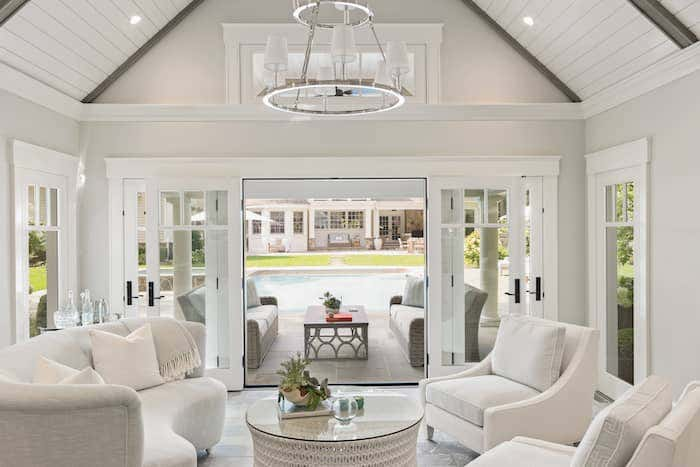 A sliding glass door and large floor to ceiling windows help to eliminate the feeling of separation between your living room and outdoor space, while Sunbrella clad sofas create a seamless transition between areas. Photo credited to Josh Goetz Photography.