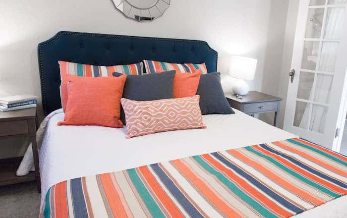 Brightly striped bedding in shades of teal, cream, and coral bring warmth to your interior design.