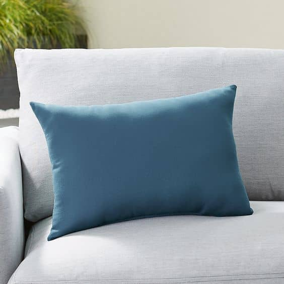 A solid outdoor throw pillow anchors your outdoor design with a pop of color and added comfort