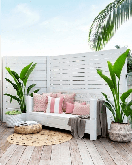 Coastal outdoor patio design with pink Sunbrella pillows