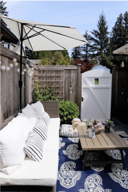 Small backyard patio design with a sofa upholstered in white Sunbrella upholstery fabric
