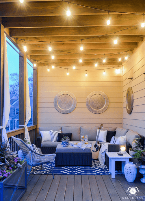 Small outdoor patio idea with hanging lights and outdoor furniture in Sunbrella upholstery fabric