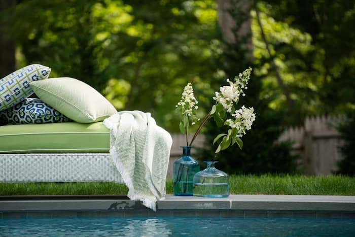 Green Sunbrella outdoor waterproof upholstery fabrics, outdoor pillows, and green throw by the pool