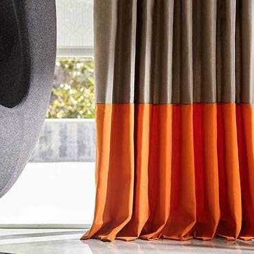 Orange and brown sunbrella drapes on a window