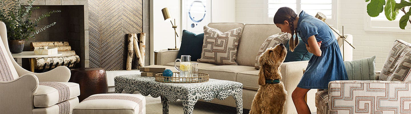 Young girl and dog playing in living room with patterned pillows and cream couches