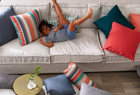young child playing on beige couch with coral and blue pillows