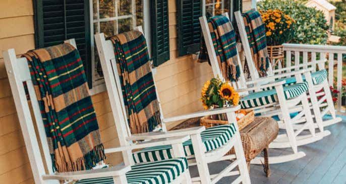 Easy ideas for front porch decorating include adding cozy throw blankets to accent your bright cushions from warmer months, such as these made from all-weather Sunbrella fabrics.