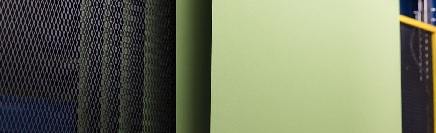 Green fabric panel hanging in front of metal mesh