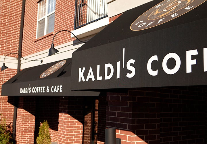 Black awnings with logo and text above a coffee shop