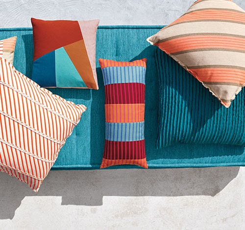 Topdown view of assortment of bright blue and orange outdoor cushions