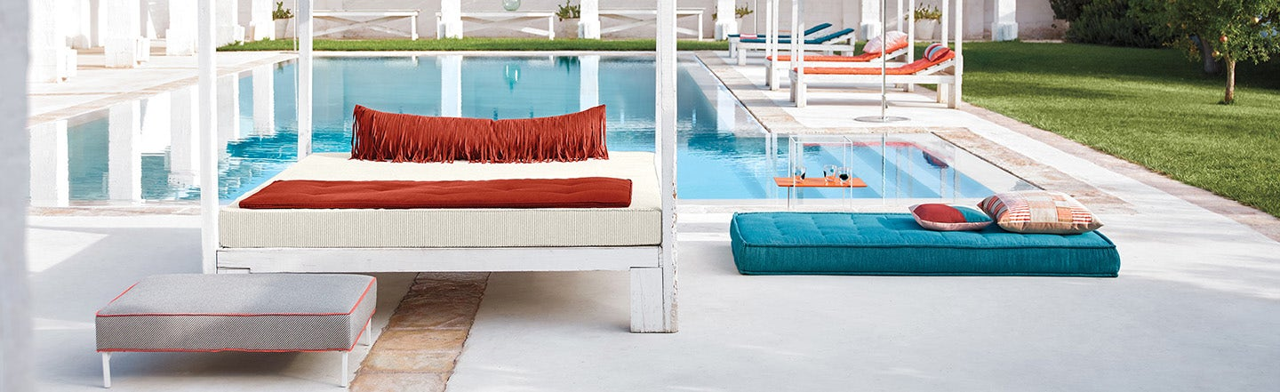 Poolside furniture featuring blue and orange Sunbrella cushion