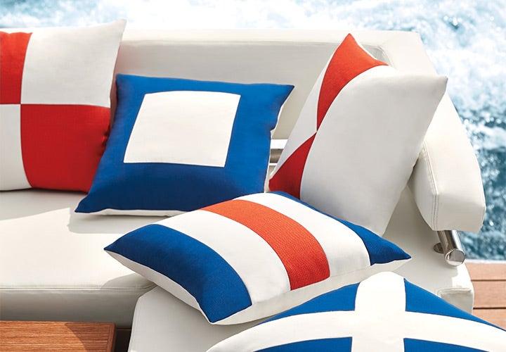 Orange, blue, and white pillows on boat sofa