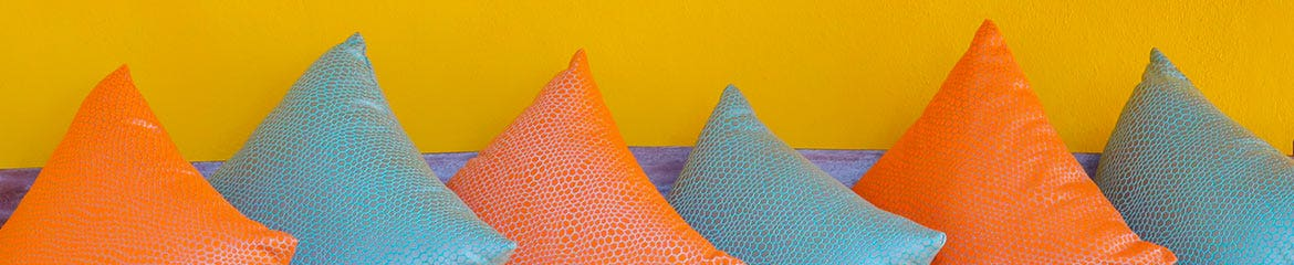 Alternating orange and blue pillows against a yellow wall.