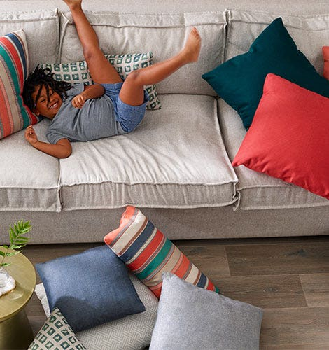 Child playing on a couch with several pillows.