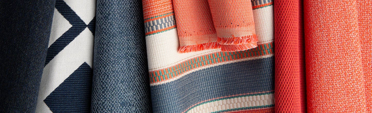 Orange and blue patterned woven fabrics hanging