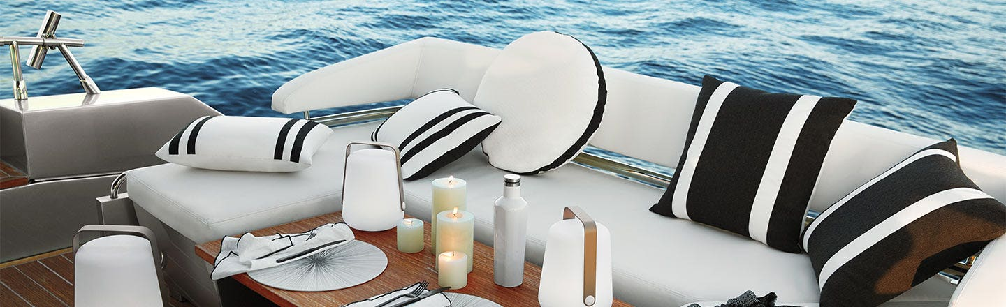 White boat sofa with pillows and candles