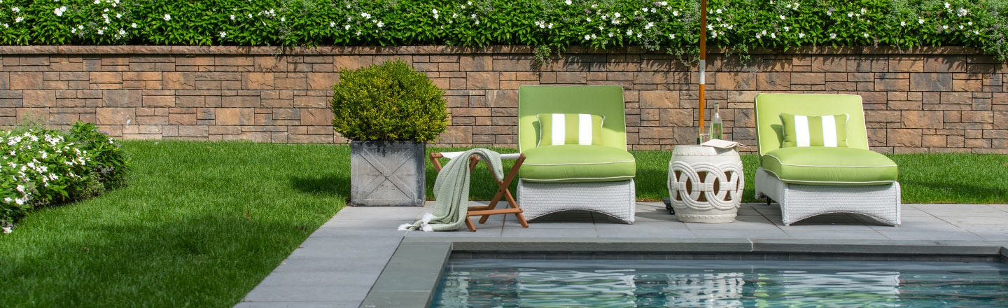 Green cushions on poolside patio furniture