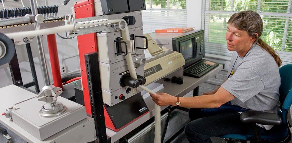 Factory worker testing fabric machine