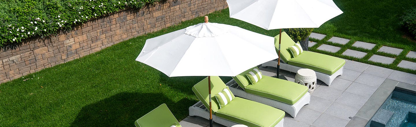White umbrellas over green pool chairs