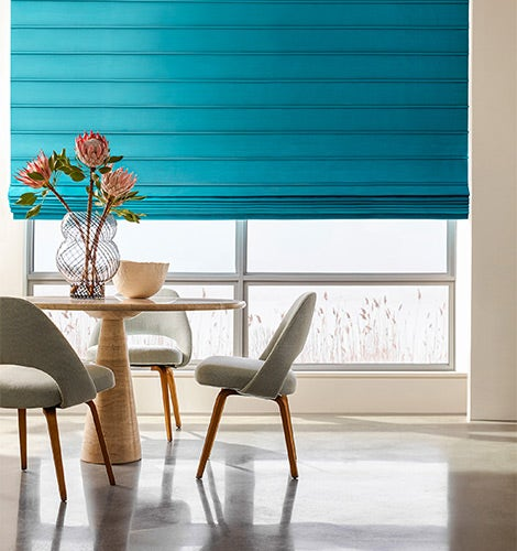 Bright teal drapes covering windows in a dining area